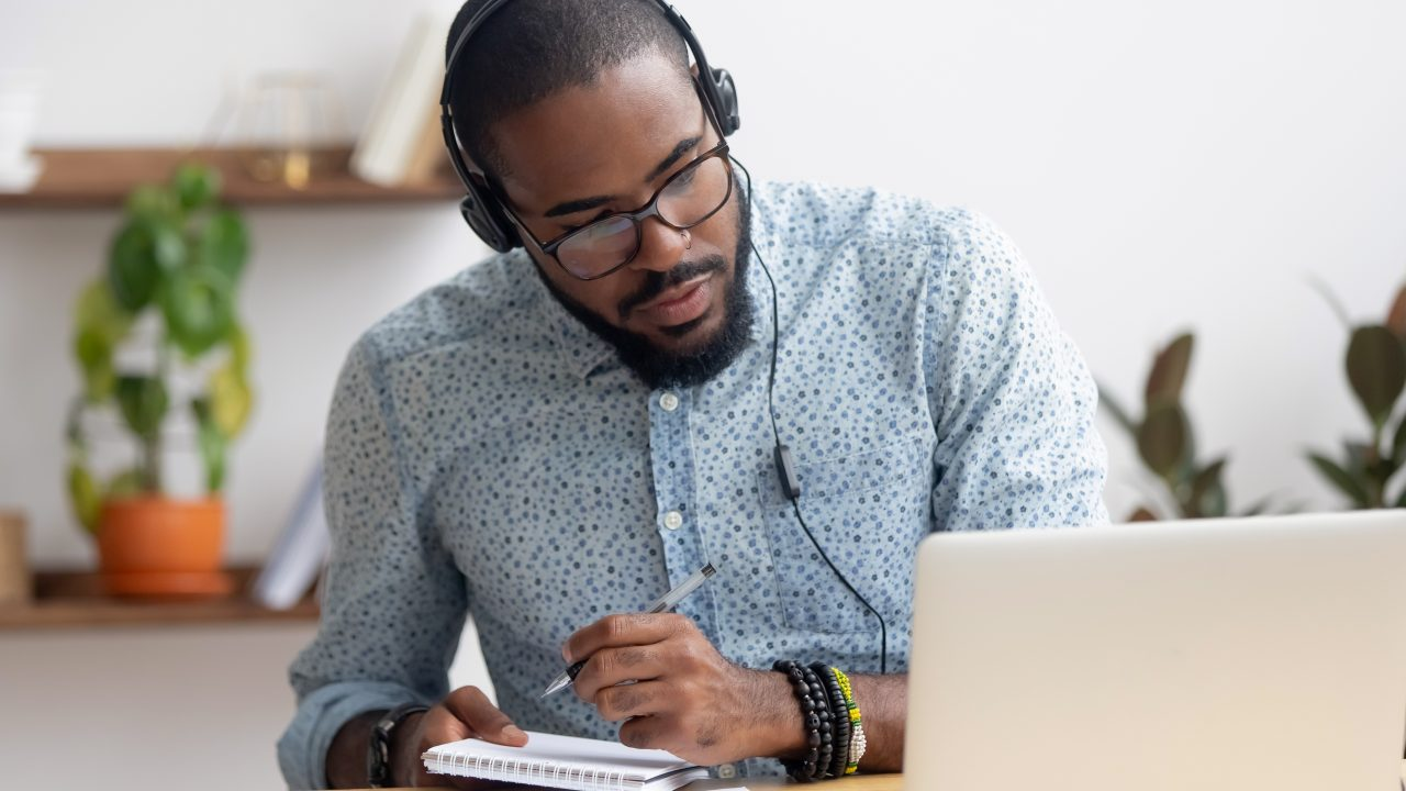 Man wearing headphones, writing on notebook while looking at a laptop.